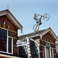 Nederland, Zaandam , 5 juli 2013.<br /> Wandeling door de binnenstad van Zaandam.  <br /> Starten bij De Werf aan de Oostzijde. Daarvandaan kun je lopen op een soort boulevard tussen de flats en het water. De eerste stop is De Fabriek, filmhuis en eetcafé met terras aan de Zaan met uitzicht op de sluis. Daarna de sluis zelf.<br /> Dan langs het winkelgebied richting de Koekfabriek: Het oude Verkade pand dat is verbouwd en waar nu de bieb en sportschool en restaurant etc. in zitten.<br /> (Dat is aan de overkant van het startpunt) en misschien nog de Zwaardemaker meepakken aan de Oostzijde. Dat is een oud pakhuis die Rochdale enige jaren geleden heeft verbouwt tot appartementen met een stukje Nieuwbouw.<br /> Ook doen: het Russische buurtje vlakbij de Zaan. Dit jaar staat Rusland in de schijnwerpers en Zaandam heeft een speciale band met Rusland, vanwege het Czaar Peterhuisje en de Russische buurt. <br /> Op de foto: beeld van een fietser op een zolderdak in de  Russische buurt die vanaf het standbeeld van tsaar Peter naar het Tsaar Peter huisje voeren. <br /> Foto:Jean-Pierre Jans