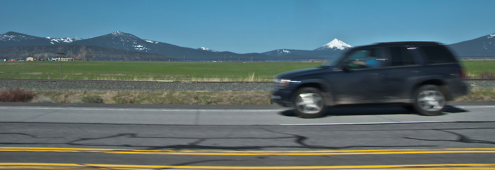 scene along a cross country trip with in a classic Mini Cooper auto - Cascade Range volcano and auto along US 97