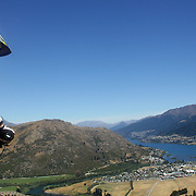 A competitor in action during the NZBNZ South Island Downhill Cup mountain bike downhill series held on The Remarkables face with a stunning backdrop of the Wakatipu Basin. 150 riders took part in the two day event.  Queenstown, Otago, New Zealand. 9th January 2012. Photo Tim Clayton
