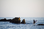 A surfer stands up with his surfboard on a rock outcrop off of Laguna Beach, California.