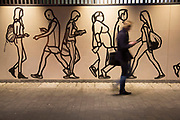 Hoarding depicting people walking by interacts with commuters passing by during rush hour during works at an underground station in London, England, United Kingdom.