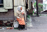 """A """"Babushka"""" (Russian old woman) keeps an eye on things from her property in Tomsk, Siberia. June 2001."""