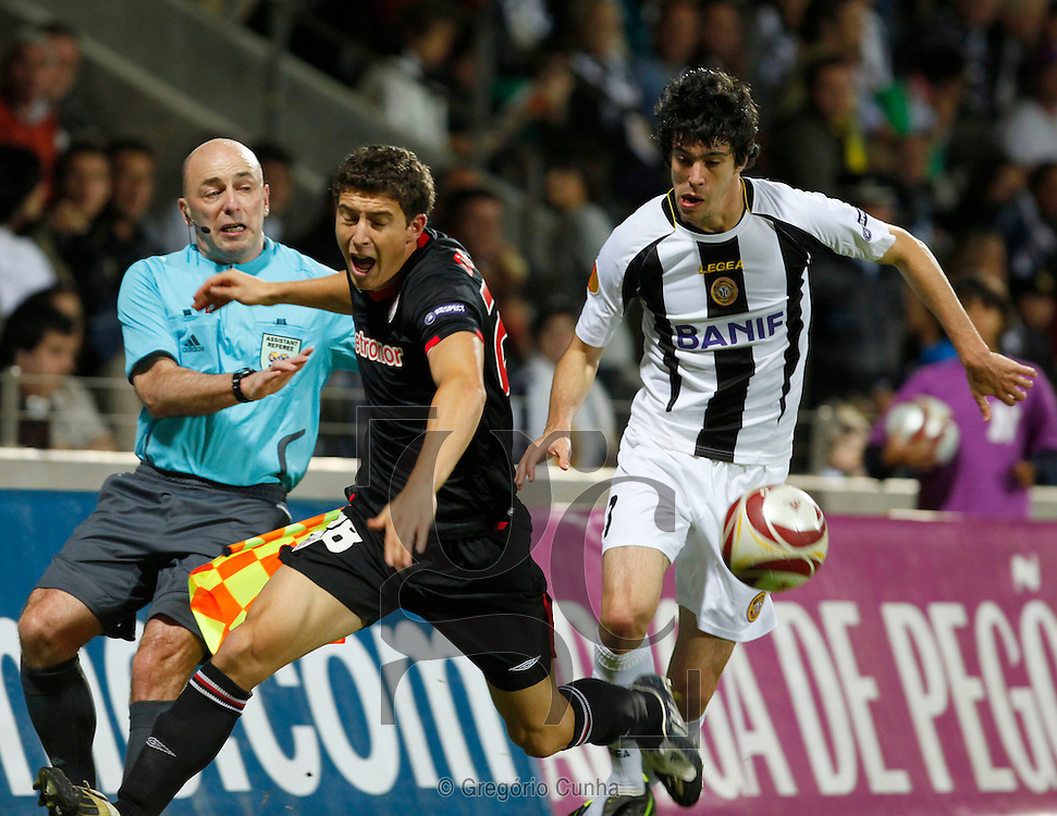 Athletic Bilbao's Oscar de Marcos, center, challenges Nacional's Felipe Lopes from Brazil, with an unidentified assistant referee at left, during a Europa League, Group L soccer match Thursday, Nov. 5, 2009 at Nacional's Madeira Stadium in Funchal, Madeira Island, Portugal.Photo Gregorio Cunha.Liga Europa, Estadio da Madeira.Nacional vs Atletico Bilbao.Oscar de Marcos e Felipe Lopes.Foto Gregorio Cunha