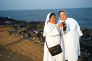 Two Nuns check their digital camera after photographing on the beach, Pondicherry, India. Pondicherry now Puducherry is a Union Territory of India and was a French territory until 1954 legally on 16 August 1962. The French Quarter of the town retains a strong French influence in terms of architecture and culture.