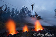 lava emanating from Pu'u O'o on Kilauea Volcano, glows from a new fissure ( Fissure 13 ) that has opened up in the middle of Leilani Avenue in Leilani Estates subdivision, near Pahoa, Puna District, Hawaii ( the Big Island ), Hawaiian Islands, U.S.A., while insulation burns off electric power lines in the background