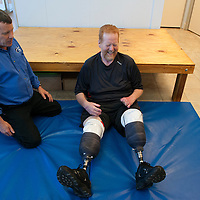 Physical Therapist Tim Marahrens looks on as Lee Spearman laughs while trying to get up from the floor at First Step Therapy in Wilmington, N.C., April 3, 2014. Lee Spearman was hospitalized in December of 2013 with an infection that was ravaging his body and almost took his life and resulted in having both of his legs amputated below the knee and all the fingers on his left hand. Photo By Mike Spencer/StarNews Media