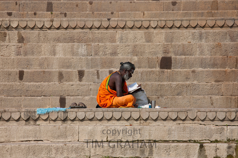 Hindu Sadhu holy man with traditional robe reads on steps of the Ghats in holy city of Varanasi, Benares, Northern India