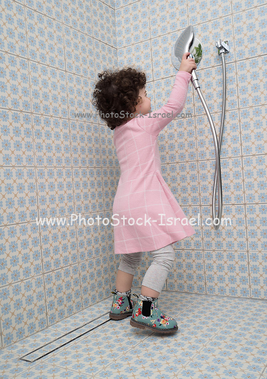 Fully dressed, toddler girl plays in the shower