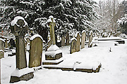 Snow covered gravestones in Hampstead Parish churchyard, London, United Kingdom