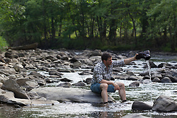 rugged man outdoors at a stream in Upstate New York getting the water out of his hiking boot