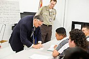 """06 NOVEMBER 2006 - PHOENIX, AZ: Maricopa County Sheriff JOE ARPAIO signs an autograph for a Spanish speaking prisoner in the county jail.  Sheriff Arpaio is offering intensive two week English classes for Spanish speaking prisoners in the Maricopa County Jails so county prisoners can communicate with Detention Officers. The classes teach """"jail English"""" so inmates can report medical problems, request their lawyers, request bedding etc. There are more than 1,000 illegal immigrants in the county jail system. In 2011, the US Department of Justice issued a report highly critical of the Maricopa County Sheriff's Department and the jails. The DOJ said the Sheriff's Dept. engages in widespread discrimination against Latinos during traffic stops and immigration enforcement, violates the rights of Spanish speaking prisoners in the jails and retaliates against the Sheriff's political opponents.      PHOTO BY JACK KURTZ"""