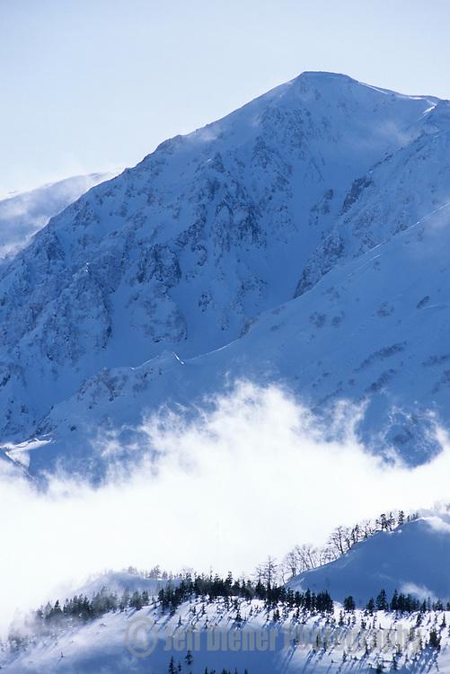 Clouds hug the high peaks of the Northern Japan Alps in the Hakuba Valley of Japan.
