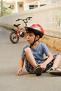 Young boy of six on the ground after falling off his bicycle