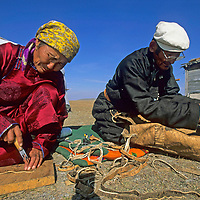 MONGOLIA, Darhad Valley. Battogtokh (L) & her husband Dorjgoo sew saddle bags for migration.  Both are veterinarians-turned-herders.