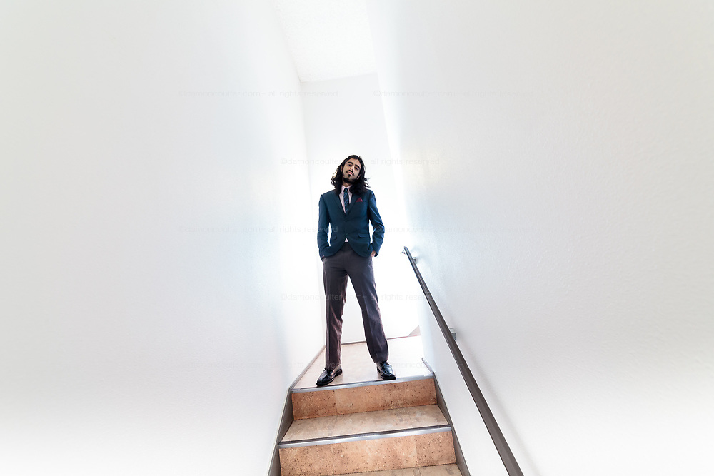 Portrait of British musician, Girish Malhotra in a white stairwell in Tokyo, Japan. Friday October 30th 2015