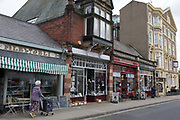 An elderly shopper walks past typical Edwardian seaside shop fronts, on 14th July 2017, at Filey, North Yorkshire, England.