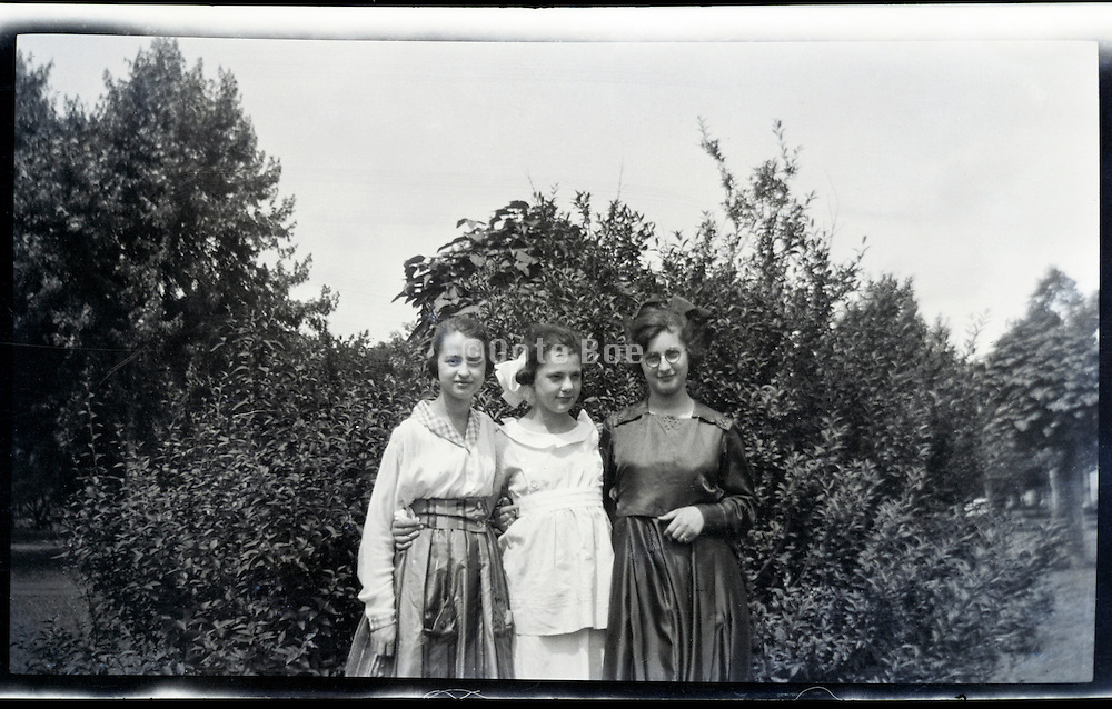 two young adult girls and adult woman in outdoor garden 1920s USA