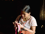 Porpae, an unmarried Ko Pala ethnic minority girl sews her traditional costume at home, Ban Honglerk, Phongsaly Province, Lao PDR. One of the most ethnically diverse countries in Southeast Asia, Laos has 49 officially recognised ethnic groups although there are many more self-identified and sub groups. These groups are distinguished by their own customs, beliefs and rituals. Details down to the embroidery on a shirt, the colour of the trim and the type of skirt all help signify the wearer's ethnic and clan affiliations.