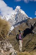 A trekker pauses under Mount Jirishanca (Icy Beak of the Hummingbird, 6126 m or 20,098 feet) in the Cordillera Huayhuash, Andes Mountains, Peru, South America. Day 3 of 9 days trekking around the Cordillera Huayhuash.