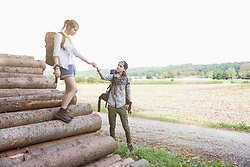 Young couple preparing to continue their hiking on wood pile, Bavaria, Germany