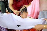 A monk shaves the boys head and the hair is caught in a white cloth held by his parents during a Shinbyu Novice Ceremony on 25th March 2016 in Loikaw, Kayah State, Myanmar. In Myanmar, it is customary for boys to enter the monastery as a Buddhist novice between the age of ten and 20 years old although they can be as young as four, for at least one week. During the ceremony, which lasts two or sometimes three days, the boys are dressed and made-up to be a prince and paraded through the village before being ordained as novice monks.