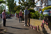 As the Coronavirus lockdown continues over the May Bank Holiday, the nation commemorates the 75th anniversary of VE Day (Victory in Europe Day, the day that Germany officially surrendered in 1945) and in Dulwich, neighbours and residents emerge from their homes to party while still observing social distancing rules. Local residents respecting social distancing, chat after together singing the wartime morale-raising songs of Dame Vera Lynn: 'White Cliffs of Dover' and 'We'll Meet Again', on 8th May 2020, in London, England.