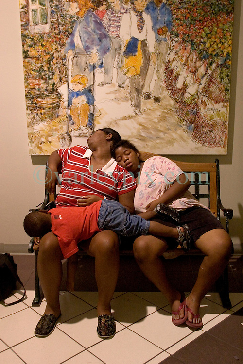31 August, 2005. New Orleans Louisiana. <br /> Hurricane Katrina.  Refugees from Hurricane Katrina sleep underneath a painting at the Regency plaza before boarding busses to take them out of New Orleans.<br /> Photo Credit: Charlie Varley/varleypix.com