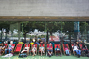 People relaxing on deck chairs outside the National Theatre. The South Bank is a significant arts and entertainment district, and home to an endless list of activities for Londoners, visitors and tourists alike.