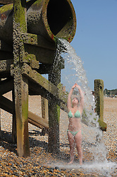 © Licensed to London News Pictures. 18/07/2013<br /> As the heatwave continues across the UK today (18.07.2013)<br /> People enjoy the  heatwave  in Hastings,East Sussex.<br /> Poppy age 20 from Hastings cooling off under the spring water run off on Hastings beach.<br />  Photo credit :Grant Falvey/LNP