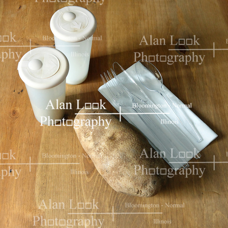 18 February 2016:   Studio - Potato #003. A single baking potato with plastic ware, a paper napkin and salt and pepper in shakers sit on a wooden table top.