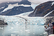 Tourists look out at the Surprise glacier with the medial moraine running down the middle and brash ice floating in Harriman Fjord, near Whittier, Alaska. Surprise Glacier is the most active calving tidewater glacier in Prince William Sound.