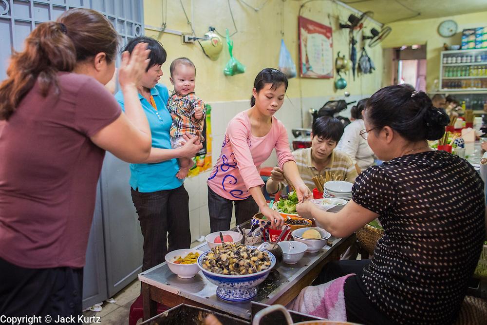 05 APRIL 2012 - HANOI, VIETNAM:   A woman in a noodle shop entertains a baby in Hanoi, the capital of Vietnam.   PHOTO BY JACK KURTZ