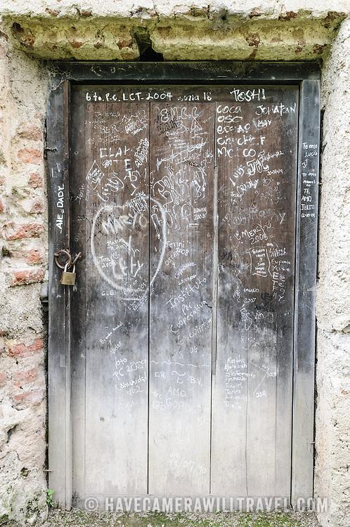 Graffiti on a door at Iglesia y Convento de La Recolección in Antigua, Guatemala.