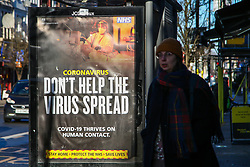© Licensed to London News Pictures. 25/01/2021. London, UK. A woman walks past the government's 'Don't Help The Virus Spread' publicity campaign poster in north London. Prime Minister Boris Johnson is set to approve plans for Australia-style hotel quarantines for anybody returning from abroad, who will have to spend ten days isolating in a hotel at their own expense. Photo credit: Dinendra Haria/LNP