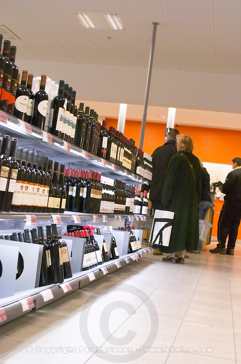 The interior of Systembolaget, the Swedish retail monopoly stores for alcohol wine beer spirits with bottles displayed on self service shelves. People standing in line at the check out counter waiting to pay. Stockholm, Sweden, Sverige, Europe