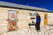 Hiker at the summit hut and register on Mount Whitney, Sequoia National Park, Sierra Nevada Mountains, California USA