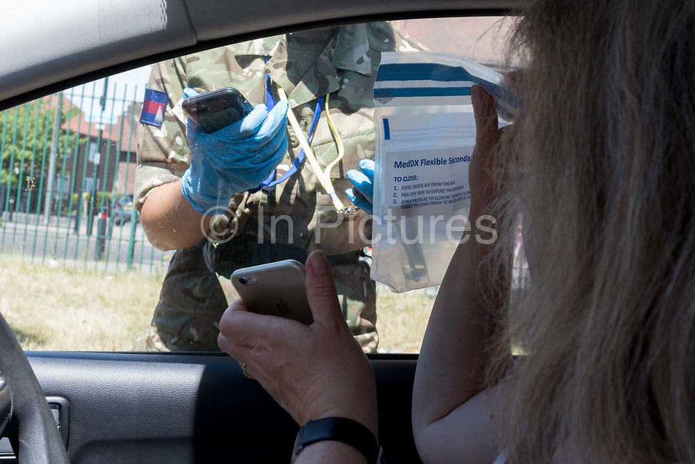 A middle-aged lady follows instructions from army personnel from the drivers seat of her car after a self-administered Coronavirus COVID-19 test in south London. There are four steps to the self-administered Covid-19 test inserting a swab into the nose and throat which the public works through in their car, windows up and all communications with army personnel via phone, in a south London leisure centre, on 2nd June 2020, in London, England. The kit provided consists of a booklet, plastic bag, swab, vial, bar codes and a sealable biohazard bag. The swab sample is taken from the back of the throat and nasal passage with the contents sealed and returned to soldiers through a narrow window. The whole process takes between 5-10mins with results available within 48hrs.