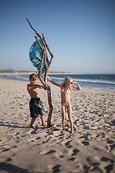 Two children playing with wood on the beach, Viana do Castelo, Norte Region, Portugal