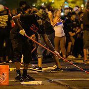 """Artist paint """"Defund The Police"""" on 16th Street. Thousands of Black Lives Matter Protesters march from multiple locations and descended onto the newly name Black Lives Matter plaza on 16th and H Street to protest of the killing of George Floyd in police custody, on Saturday, June 6, 2020."""