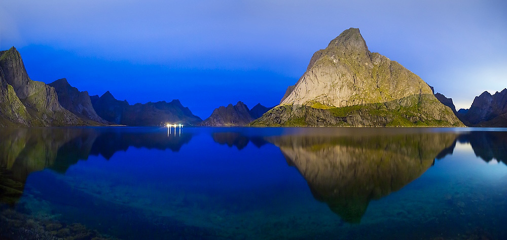 Cliffs glow at night above Reinefjorden, lit by the lights of nearby Reine, Moskenesoya, Lofoten Islands, Norway. Lights of Vindstad are visible across the fjord.