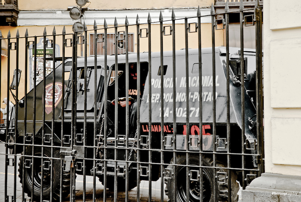 A police officer reads while on duty in an armored car outside Saint Francis Monastery in Lima, Peru