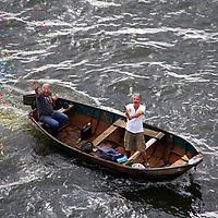 Europe, Netherlands, Amsterdam. Boaters celebrate a cruiseship sailaway from Amsterdam.