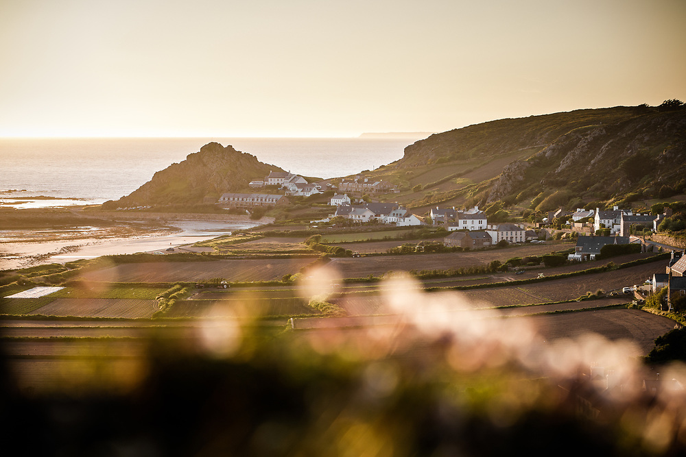 View of the sea at L'Etacq across fields and countryside in rural St Ouen, Jersey