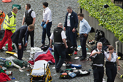 Conservative MP Tobias Ellwood (left) stands amongst the emergency services at the scene outside the Palace of Westminster, London, after policeman has been stabbed and his apparent attacker shot by officers in a major security incident at the Houses of Parliament.