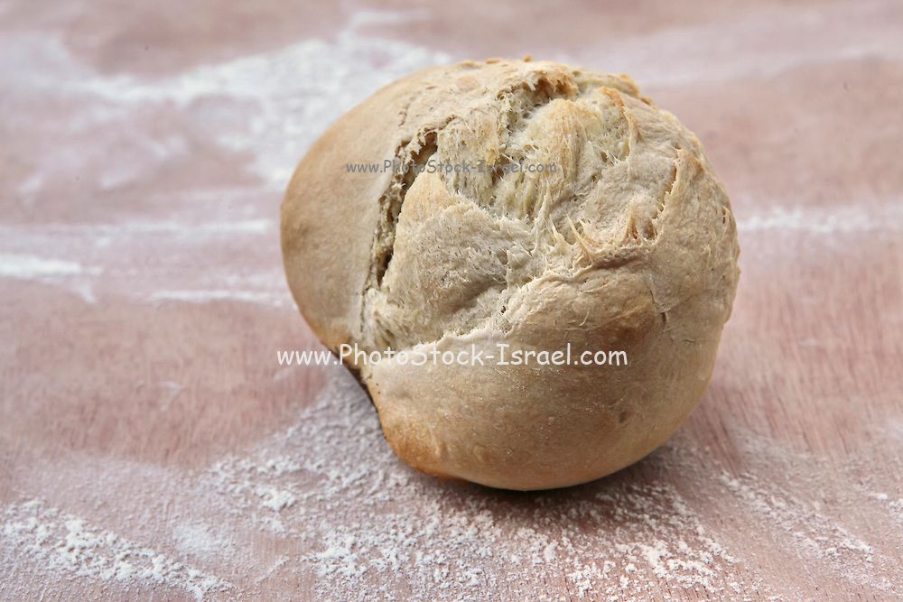 Freshly baked roll on a flour covered board in a bakery