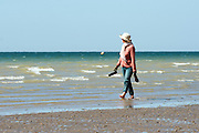 © Licensed to London News Pictures. 03/07/2014. Bognor Regis, UK. A woman wrapped against the sun walks along the coastline.  People enjoy the hot sunny weather at the seaside resort of Bognor Regis today 3rd July 2014. Forecasters are predicting it to be the hottest day of 2014 so far. Photo credit : Stephen Simpson/LNP