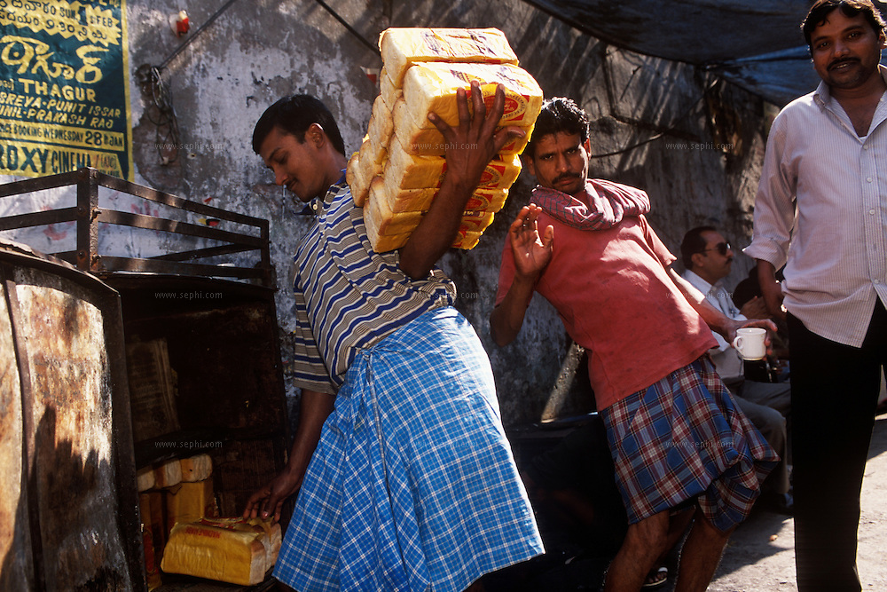 A bread seller piles up bread on his arm as another man who noticed the camera 'bends over backwards' to get into the frame. Kolkata, January 2004