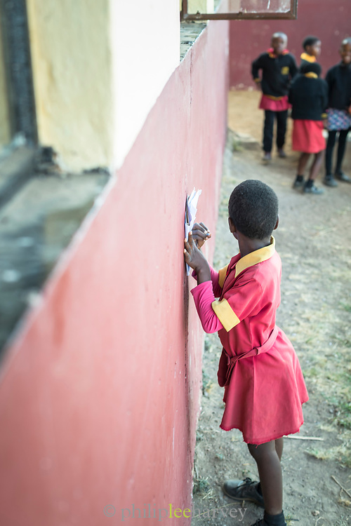 Close-up of pupil doing school work against wall on paper at local village school, in Lubombo Region, Eswatini