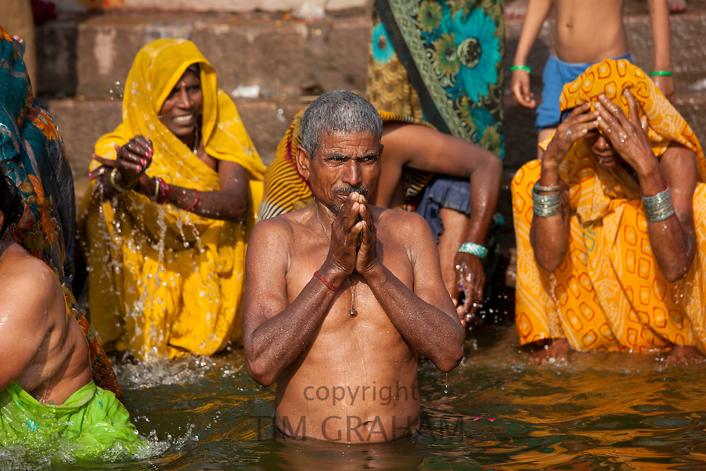 Indian Hindu pilgrims bathing and praying in The Ganges River at Dashashwamedh Ghat in Holy City of Varanasi, Benares, India