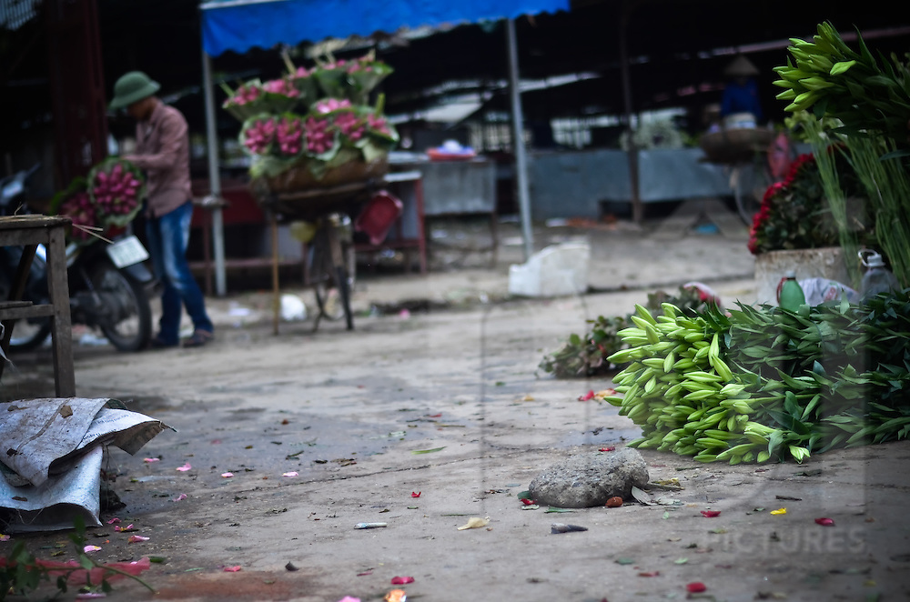 Scene of the flower market when it's almost empty, with flowers on the streets and a man packing some flowers in the backgrounds.